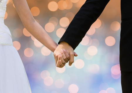 Digital composite of Couple Hands holding wedding couple with sparkling light bokeh background