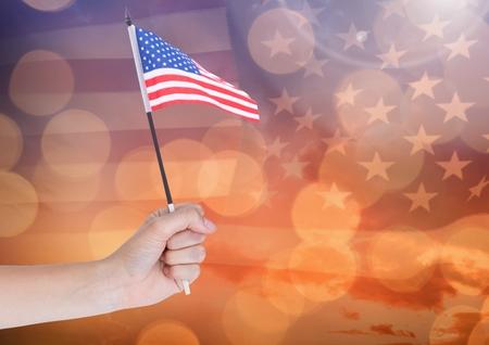 gold en: Digital composite of Hand holding American flag with sparkling light bokeh background