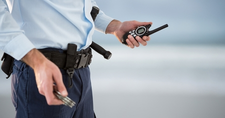 Digital composite of security guard with walkie-talkie and cuffs. blurred back Stock Photo