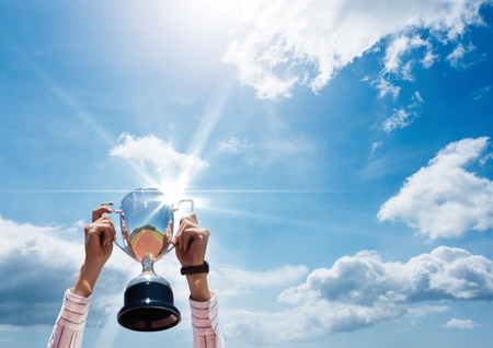 Digital composite of business hands with trophy in front of a blue sky
