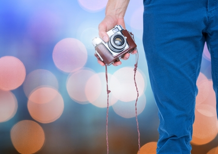 Digital composite of Hand holding camera with sparkling light bokeh background Stock Photo