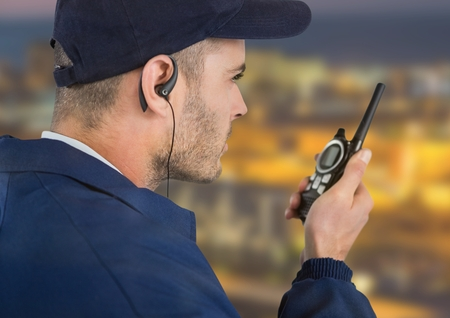 earpiece: Digital composite of security guard with headphone and walkie-talkie with a blurred night background