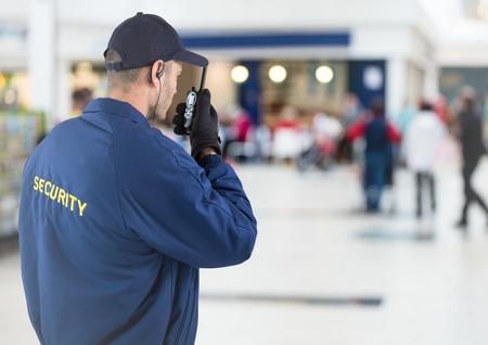 Digital-Zusammensetzung von Rückseite des Sicherheitsbeamten mit Funksprechgerät gegen undeutliches Einkaufszentrum Standard-Bild