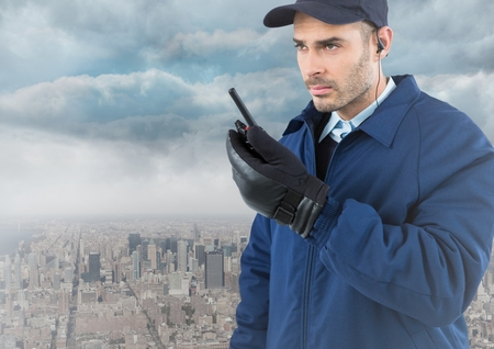 Digital composite of Security guard with walkie talkie against skyline and clouds