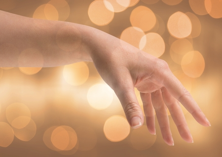 gold en: Digital composite of Hand reaching kindly with sparkling light bokeh background