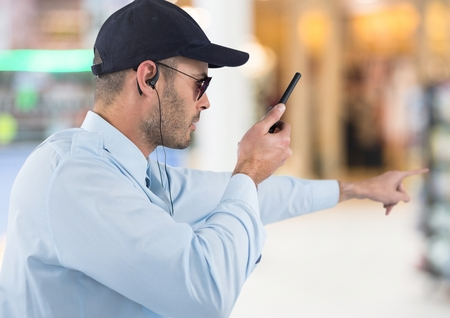 Digital composite of Security guard with walkie talkie pointing against blurry shopping centre
