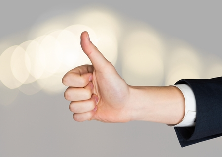Digital composite of Hand Thumbs up with sparkling light bokeh background Stock Photo