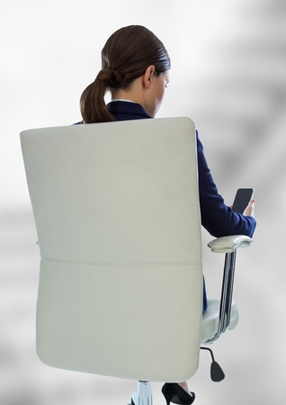 Digital composite of Back of seated business woman with phone against blurry grey stairs