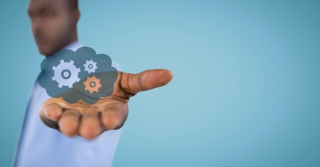 Digital composite of Business man with blue cloud and gear graphic in outstretched hand against blue background