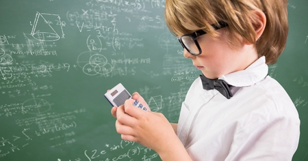 Digital composite of Boy with calculator against green chalkboard with math doodles