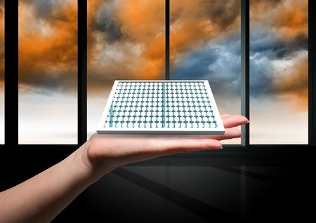 Digital composite of solar panel on hand inside a building.