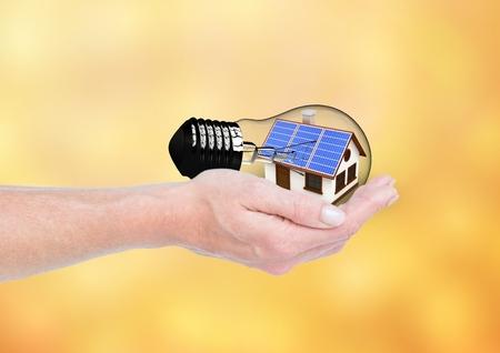 Digital composite of solar panel house inside a light on hand. Orangeyellow background