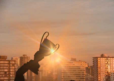 Digital composite of business hand with trophy (shade). city sunset Stock Photo