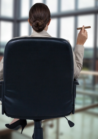 Digital composite of Back of seated business woman smoking cigar in blurry office