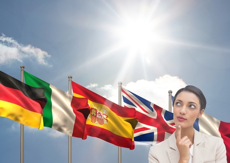 Digital composite of main language flags behind young businesswoman. Sky Stock Photo