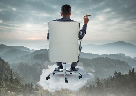 Digital composite of Businessman Back Sitting in Chair with cigar on cloud over mountain landscape Stock Photo