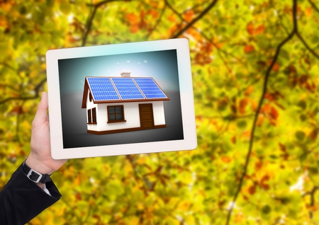 Digital composite of solar panel house on tablet with businesswoman hand in the park