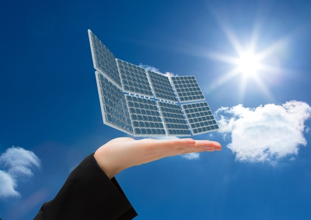 Digital composite of solar panel on hand in the sky