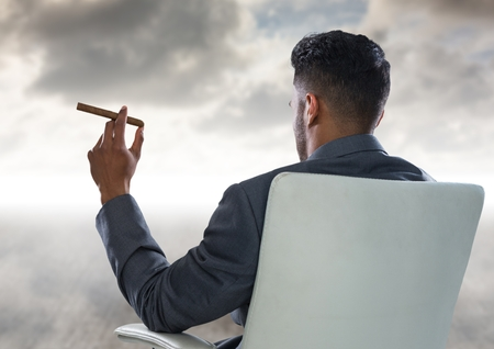 joven fumando: Digital composite of Back of seated business man smoking cigar and looking at clouds