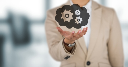 Digital composite of Business woman mid section with hand out and cloud with gears graphic against blurry grey office