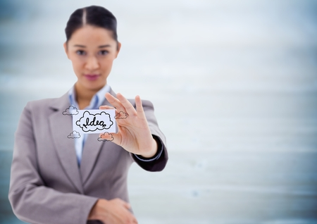 Digital composite of Business woman holding out card showing idea doodles against blurry blue wood panel Stock Photo