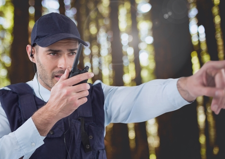 earpiece: Digital composite of Security man outside in forest