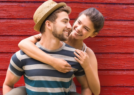Digital composite of young couple looking each other with red wood background