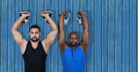 Digital composite of 2 fitness man with the wights with blue wood background Stock Photo