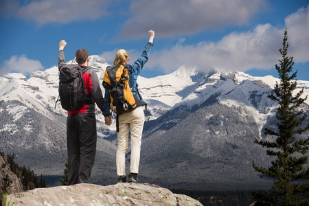 Digital composite of Couple raising their hands on the top of mountains in front of snow-covered mountains