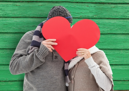 affection: Digital composite of couple behind the heart with green wood background