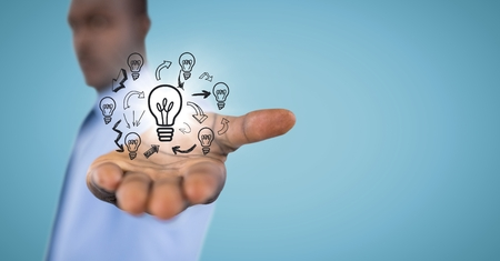 Digital composite of Business man mid section with lightbulb doodles and flare against blue background
