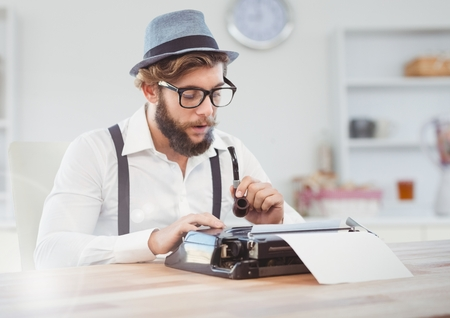 Digital composite of Hipster man  on typewriter in bright room Stock Photo