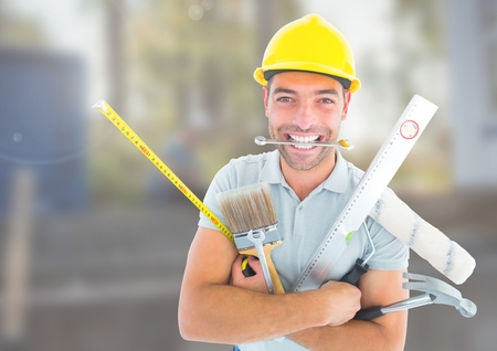 Digital composite of Construction Worker with tools in front of construction site Stock Photo