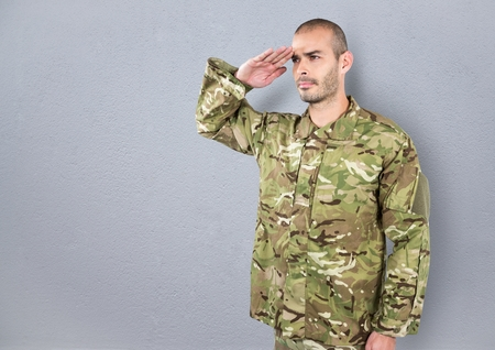 Digital composite of soldier saluting. concrete wall Stock Photo