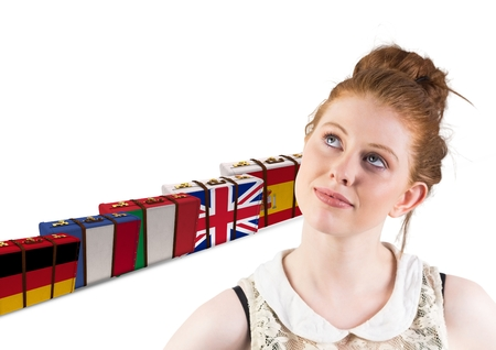 Digital composite of main language flags suitcases behind young happy woman
