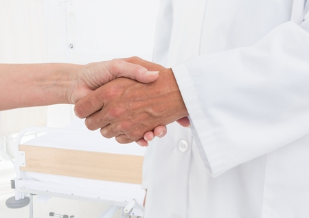 Digital composite of doctor and patient handshake in the hospital