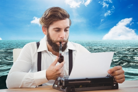Digital composite of Hipster man with a pipe reflecting on his typewriter in front of sea background