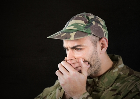 Digital composite of worried soldier foreground with cup. black background, light in his face.