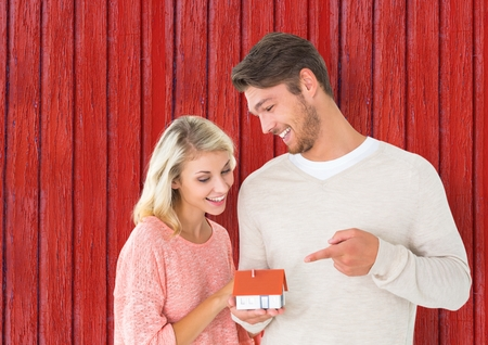 Digital composite of couple with little house in the hands with red wood background Stock Photo
