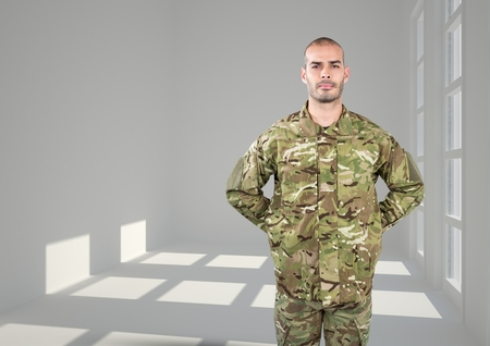 Digital composite of soldier with his hands on back. Concrete room with windows