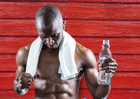 Digital composite of fitness man with water and towel with red wood background