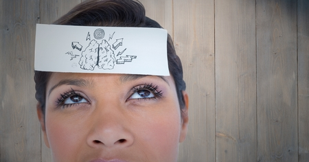 Digital composite of Close up of woman with card on head showing brain doodle against wood panel