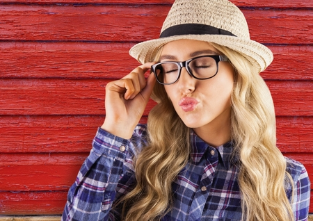 Digital composite of hipster woman with glasses sending a kiss with red wood background Stock Photo