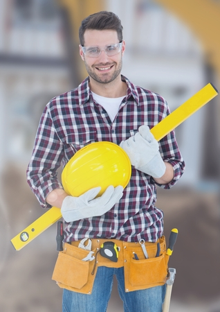 Digital composite of Construction Worker with spirit level in front of construction site