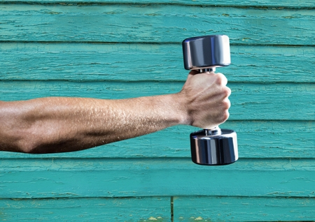 Digital composite of fitness: hand with wight with light blue wood background Stock Photo