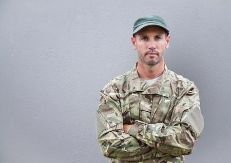 Digitale samenstelling van ernstige militair met zijn gevouwen handen. betonnen muur achter Stockfoto