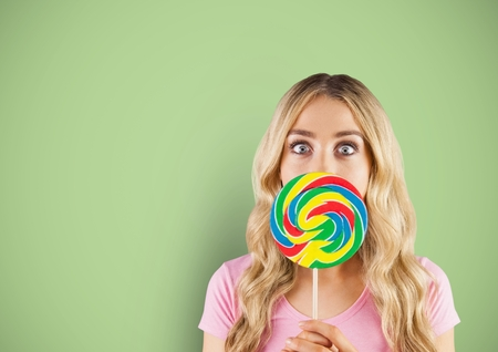 Digital composite of Blond-hair girl hidded by a candy with green background Stock Photo
