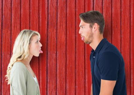 strife: Digital composite of couple funny face each other with red wood background