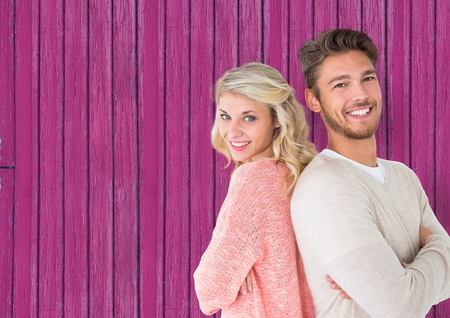 arms folded: Digital composite of couple back with back, smiling with pink wood background