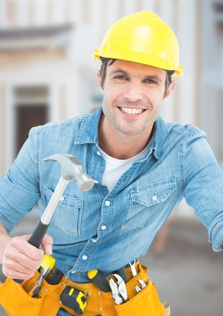 Digital composite of Carpenter with hammer on building site Stock Photo